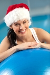 Woman resting on exercise ball with Santa hat